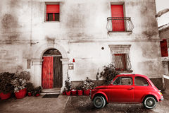 Old vintage italian scene. Small antique red car. Aging effect Royalty Free Stock Image