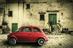 Old vintage italian scene. Small antique red car. Aging effect. An old Italian with out a small subcompact old car. Vintage scene. Historical Italian home Stock Images