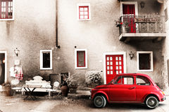 Old vintage italian scene. Small antique red car. Aging effect stock images