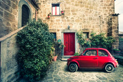 Old vintage italian scene. Small antique red car. Fiat 500. An old Italian house with outside a small subcompact old red car, fiat 500. Vintage scene Royalty Free Stock Image