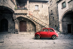 Old vintage italian scene. Small antique red car. Fiat 500. An old Italian house with outside a small subcompact old red car, fiat 500. Vintage scene Royalty Free Stock Photography