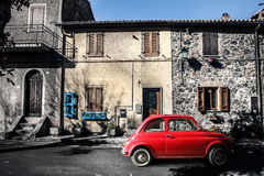 Old vintage italian scene. Small antique red car. Fiat 500. An old Italian house with outside a small subcompact old red car, fiat 500. Vintage scene Stock Image