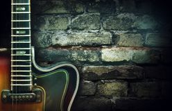 Old vintage jazz guitar on a brick wall background. Copy space. Background for concerts, festivals, music schools. Art