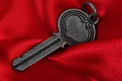 Old vintage key in red satin cloth Royalty Free Stock Photos