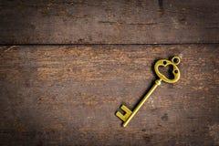 Old vintage key on wood texture background Stock Photos