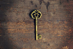 Old vintage key on wood texture background Royalty Free Stock Photography