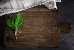 Old vintage kitchen cutting board and bunch with green sorrel. Leaves, top view Royalty Free Stock Image