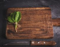 Old vintage kitchen cutting board. And bunch with green sorrel leaves, top view Stock Image