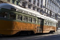Old Vintage Looking Passenger Commuter Street Car Travels along Busy Market Street in Downtown San Francisco. Orange Colored Old Vintage Looking Passenger Stock Image