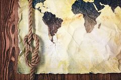 Old vintage map of the world on yellow retro stained paper with knot of rope Stock Image
