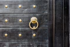 Old vintage massive wooden black door with metal locker and hand stock image