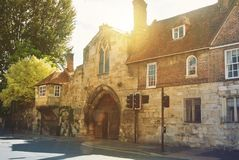 Old vintage medieval beautiful stone british house with tile roo. F and bright windows, and big trees near the asphalt road in warm evening sunset sunlight Royalty Free Stock Image