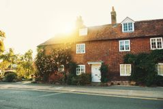 Old vintage medieval beautiful stone british house with tile roo. F and bright windows, a flowering rose garden near the asphalt road in warm evening sunset Royalty Free Stock Images