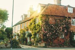 Old vintage medieval beautiful stone british house with tile roo. F and bright windows, a flowering rose garden near the asphalt road in warm evening sunset Stock Image