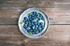 Old vintage metal plate full of fresh ripe blueberries Stock Image
