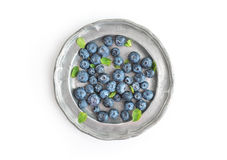 An old vintage metal plate full of fresh ripe blueberries over a Royalty Free Stock Images