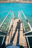 Old vintage metal wooden stairs leading to blue turquoise sea water from beach. Beautiful summer day. Swimming pool with Stock Images