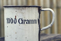 Old vintage metallic cup for 1000 grams stands on wooden background Royalty Free Stock Images