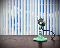 Old vintage microphone. Old green vintage microphone standing on table Stock Photography