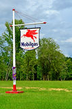 Old Vintage Mobilgas Station Sign Socony Vacuum. Old vintage tin red, white, and blue Mobil gas station sign hanging from a red and white metal post sitting in a Stock Photos