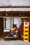 Old vintage motorcycle behind local restaurant with colourful be. June 25, 2014 Shinagawa, Tokyo, Japan : Old vintage  motorcycle behind local restaurant with Stock Photography