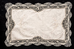Old vintage napkin with lace border on the black wooden table. Old vintage cream napkin with lace border on the black wooden table horizontal royalty free stock images