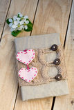Old vintage notepad Knitted sweater in beige, hearts of felt. On wooden background Stock Image