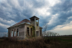 Old Vintage One Room Schoolhouse. Landscape scene of an old, vintage one room schoolhouse. Interesting metaphor for education and teaching. Clouds and sky are in Royalty Free Stock Image