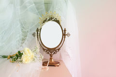Old vintage oval mirror and beautiful white wedding dress and veil on chair. Copy space for mock up, montage or design layout Stock Photography