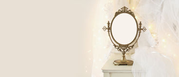 Old vintage oval mirror and beautiful white wedding dress and veil on chair with gold garland lights Royalty Free Stock Photography