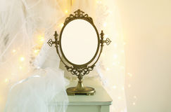 Old vintage oval mirror and beautiful white wedding dress and veil on chair with gold garland lights Stock Photos