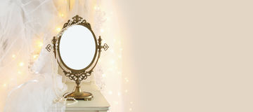 Old vintage oval mirror and beautiful white wedding dress and veil on chair with gold garland lights. Copy space for mock up, montage or design layout Stock Image
