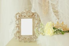 Old vintage oval mirror and beautiful white wedding dress and veil on chair Royalty Free Stock Photography