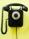 Old vintage phone. Old vintage black phone on yellow wall royalty free stock photos