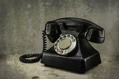 Old vintage phone with rotary disc on wooden table grunge backgr Stock Image