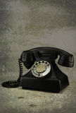 Old vintage phone with rotary disc on wooden table grunge backgr Stock Photography