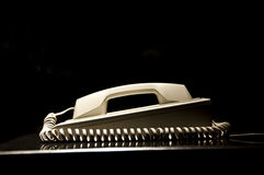 Old vintage phone with a spiral cord, black background Stock Images