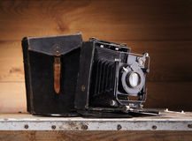 An old vintage photo camera on a wooden background Royalty Free Stock Photo