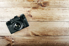 Old vintage photo camera on wooden table stock photo