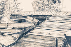 Old vintage photo. A few old simple boats on the pier Royalty Free Stock Photography