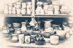 Old vintage photo.many different pottery standing on the shelves in a workshop Stock Images