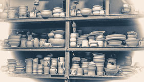 Old vintage photo.many different pottery standing on the shelves in a workshop Stock Photography