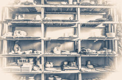 Old vintage photo.racks in a pottery workshop in which there are potter Stock Photos