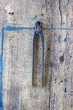 Old vintage pliers pincers against. wooden plank. Tool series stock images