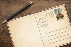 Old vintage postcard with pen on table Royalty Free Stock Photo