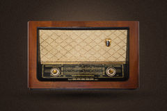 Old vintage radio. Picture of an old vintage, wooden radio isolted on brown background with noise Stock Images