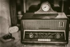 Old vintage radio receiver of the last century with rustic clock on top on window sill - front view, sepia royalty free stock photos