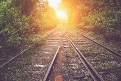 Old vintage railroad among Green trees and shrubs at sunset. Industrial landscape Stock Photo