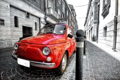 Old vintage red black and white classic parked fiat 500 car in italy rome postcard. A vintage retro fiat mini car in italy rimini colorsplash black and white and Stock Image