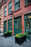 Old vintage red bricks commercial building with restaurant inside and green wooden doors. Stock Photos